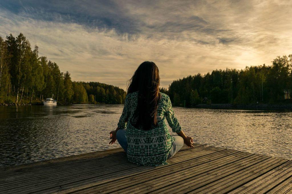 Weniger arbeiten und mehr leben - Frau macht Yoga am See