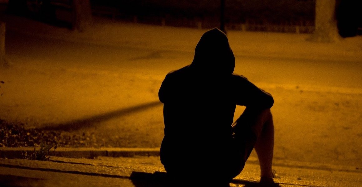Mann sitzt allein auf Straße - Selbstwertgefühl steigern